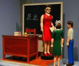 Model of a teacher and two students in a school house